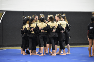 The whole FHS Gymnastics team huddles and chants together before the meet starts