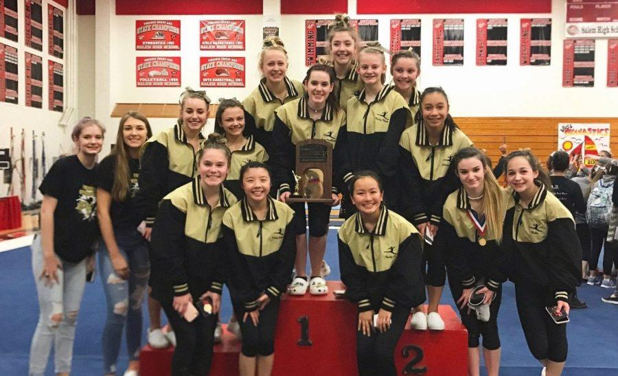 The+FHS+gymnastics+team+displays+their+trophy+at+the+state+meet+after+a+day+of+competition.+