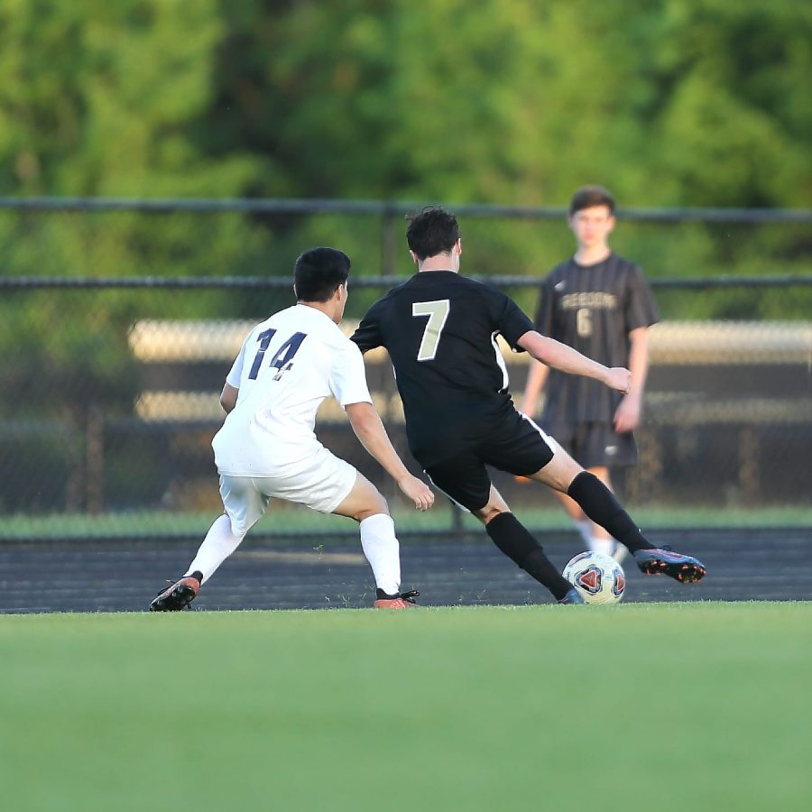 Nate Mitchell attempts to get past a Stone Bridge defender on the right wing. Photo by Chong Chung.