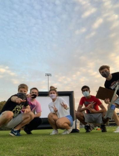 PC: Celine Sayegh Senior class officers pose in front of the jumbo movie projector at the outdoor movie night.