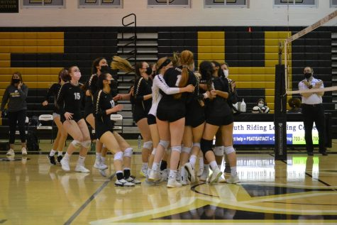 The Freedom Girls Varsity Volleyball team celebrates after winning their third set against Albemarle High School. Photo by Karen Xu