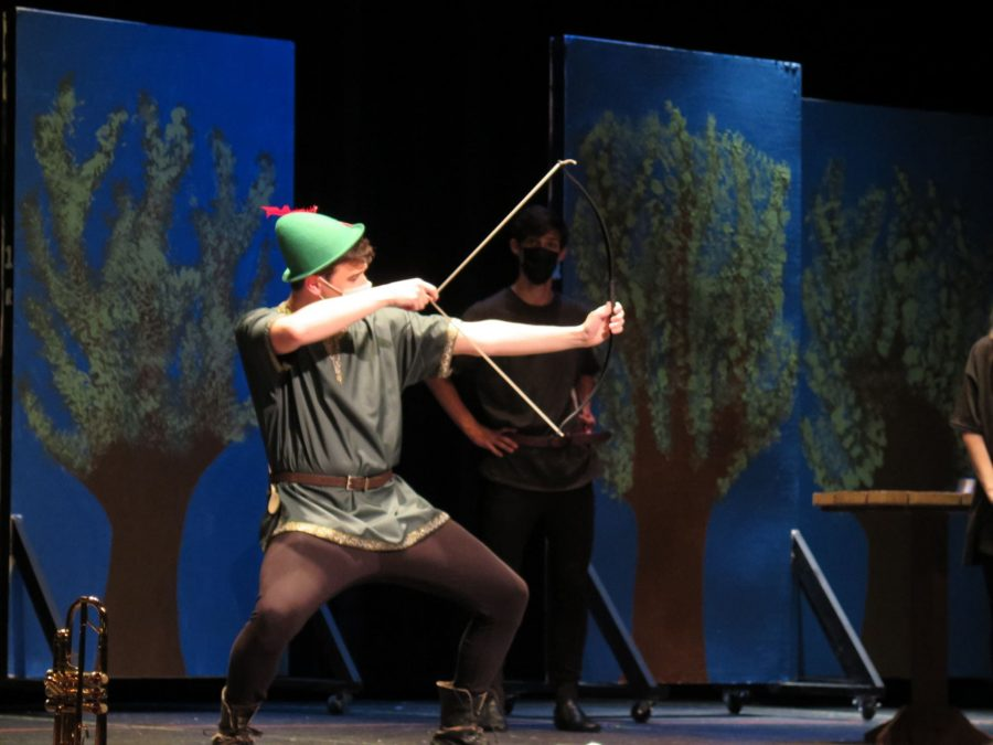Photo taken by Eliza Agi Senior Brennan Wood draws back the bow and arrow while playing the role of Robin Hood.