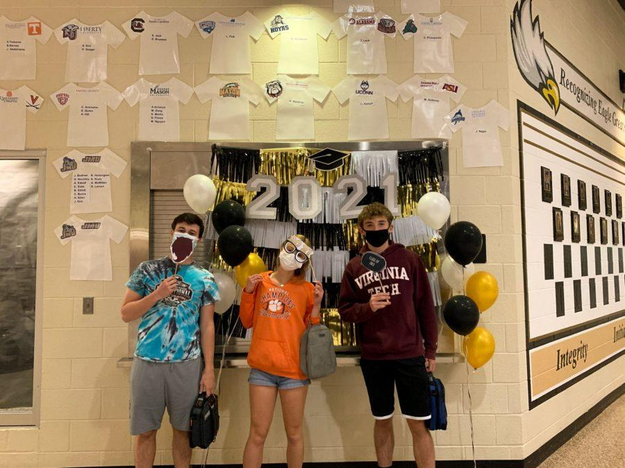 Seniors Brennan Wood, Camille Desjardins, and Josh Facey pose in front of a celebration set-up for seniors on decision day.
